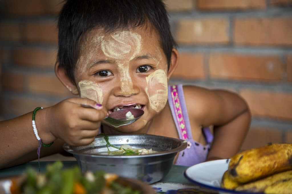 Child eats food happily after cooking demonstration at Wan Pan